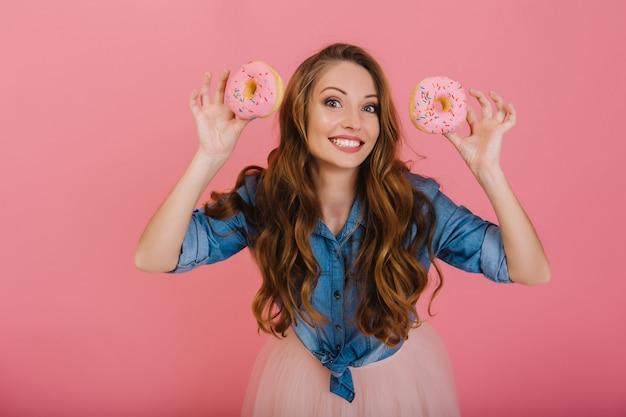 Charmantes langhaariges mädchen im trendigen outfit gebackene glasierte leckere donuts zum tee mit der familie. attraktive lockige junge frau, die aufwirft, die köstliche donuts vom bäckereigeschäft lokalisiert auf rosa hintergrund hält
