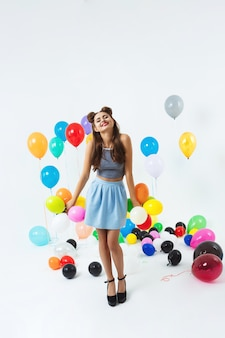 Charmantes mädchen im modeblick, der mit kleinen luftballons aufwirft