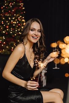 Charmantes mädchen lächelt und hält wunderkerze und ein glas mit champagner auf einer neujahrsparty