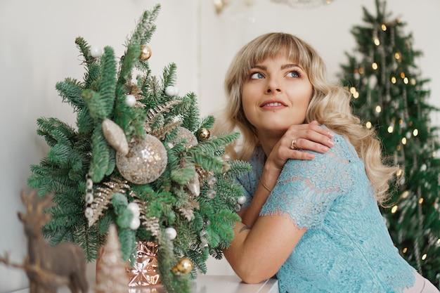 Charmantes mädchen mit schönem make-up im gesicht in gold und weiß interieur. weihnachtsferien
