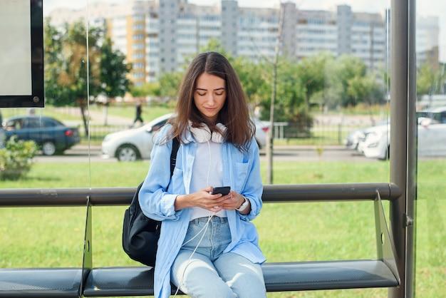 Charmantes mädchen mit trendigem look verwenden smartphone, während auf bushaltestelle warten. frau hält handy, während sie auf einer öffentlichen station sitzt und auf taxi wartet.