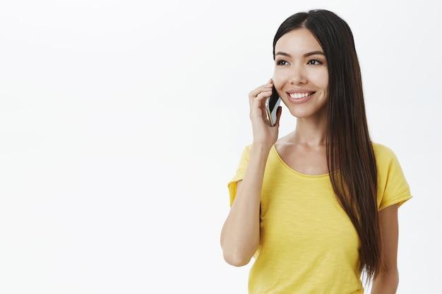 Charmantes mädchen ohne make-up hält smartphone in der nähe des ohrs und steht halb gedreht und schaut nach links mit einem breiten, sorglosen lächeln
