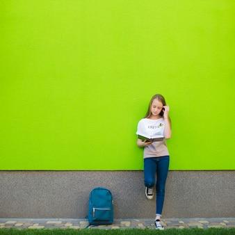Charmantes mädchen posiert mit lehrbuch