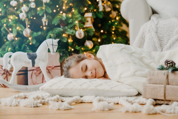Charmantes mädchen schläft auf weichen weißen kissen auf dem boden gegen geschmückten neujahrsbaum, hat angenehme träume, mit spielzeugpferd und geschenkboxen umgeben. kinder-, rest- und winterurlaubkonzept.