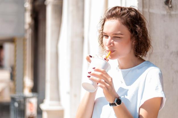 Charmantes mädchen trinkt limonade auf der straße. das konzept von tourismus, reisen, alkoholfreien getränken. gemischte medien
