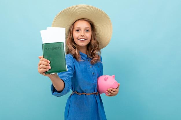 Charmantes mädchen zeigt einen pass mit tickets, hält eine rosa schwein sparbüchse und freut sich