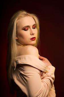 Charmantes model mit langen blonden haaren und goldenen folienmustern auf der haut, das auf schwarzem hintergrund posiert