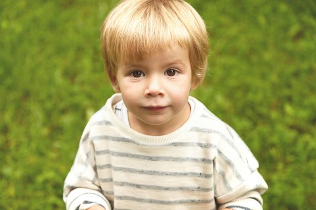 Charmantes nahaufnahme unschuldiges porträt des kleinen unschuldigen kindes. ruhiger kaukasischer junge mit blonden haaren, runden braunen augen