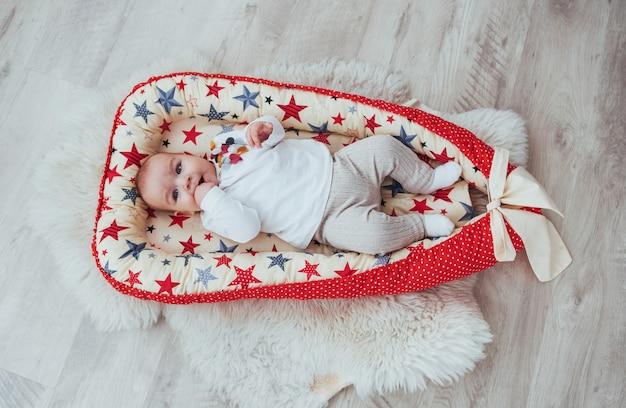 Charmantes neugeborenes baby in einer roten wiege