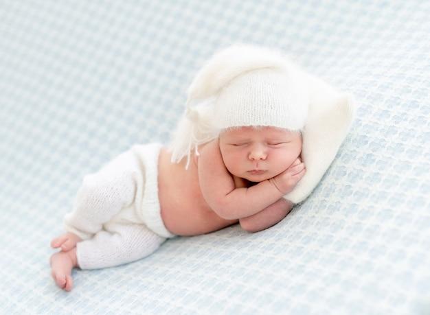 Charmantes neugeborenes, das auf seite mit dem winzigen kissen unter kopf ruht