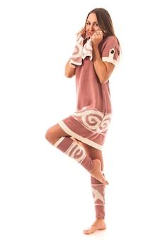 Charmantes niedliches junges mädchenmodell, das im studio im schönen strickkleid und in den leggings auf weiß aufwirft