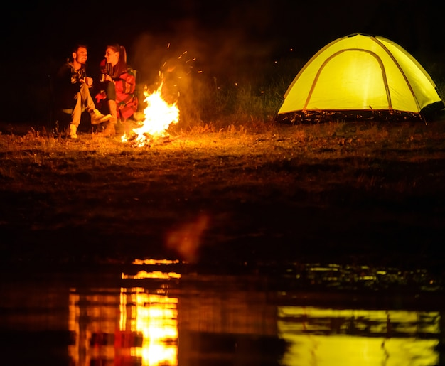 Charmantes paar, camping, sitzen am lagerfeuer