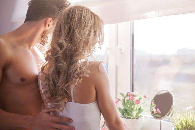 Charmantes paar, das durch das schlafzimmerfenster schaut