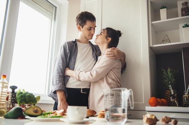 Charmantes paar, das gemeinsam das abendessen in der küche vorbereitet, während der ehemann seinen geliebten umarmt
