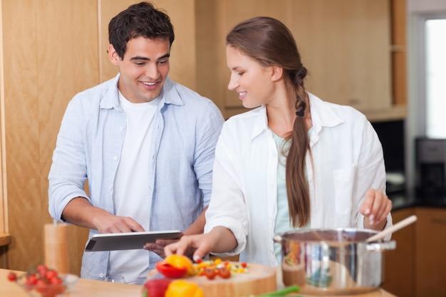 Charmantes paar mit einem tablet-computer zu kochen