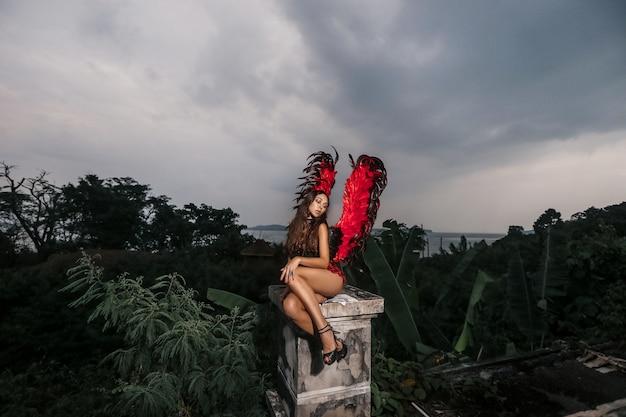 Charmantes porträt des dunklen engels mit den roten starken starken flügeln im schwarzen spitzenkleid und mit den kalten augen, die auf dem alten zerquetschten dach sitzen, kunstfoto. außenfoto mit dunklen farben