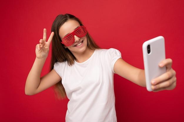 Charmantes positives junges mädchen mit weißem t-shirt und roter brille, das isoliert auf rotem hintergrund steht