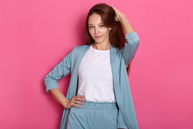 Charmantes reizendes liebes magnetisches süßes junges modell, das isoliert über rosa hintergrund im studio steht