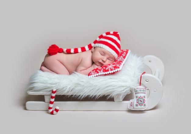 Charmantes säuglingsbaby in gestreifter haube, die auf rotem kissen auf kleinem hölzernen schlittenbett mit plüsch-weihnachtsstockspielzeug nerby schläft