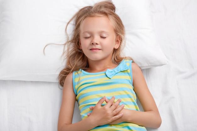 Charmantes schönes kleines kind mit unordentlichem haar, gesunder haut, hält die hände zusammen, liegt auf einem bequemen bett, hat angenehme träume während des mittagsschläfchens, kinder, gute nacht und schlafkonzept.