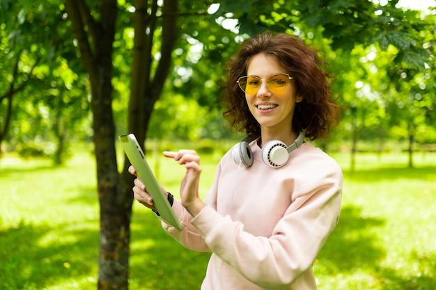 Charmantes schönes mädchen mit einer tablette während der mittagspause auf einer wand des grüns