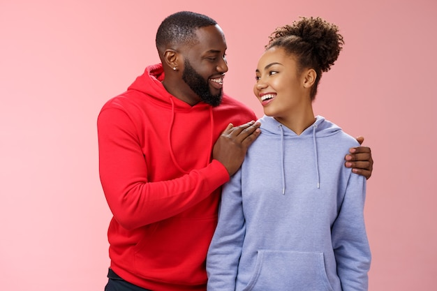 Charmantes schönes paar in liebesbeziehung unterstützen sich gegenseitig schauen fürsorglich leidenschaftliche augen lächeln breit herzerwärmend geständnis freund umarmt freundin fühlt sich sicher, stehend rosa hintergrund