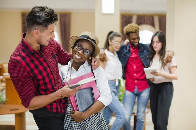 Charmantes schwarzes mädchen umarmt mit studenten