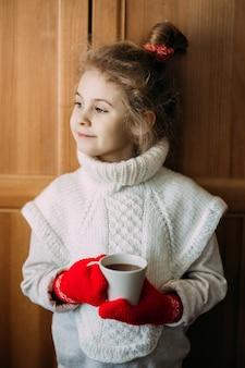 Charmantes siebenjähriges mädchen trinkt warmen tee und steht neben dem fenster. sie trägt einen warmen strickpullover, ihre hände sind in roten strickhandschuhen. weihnachtszeit.