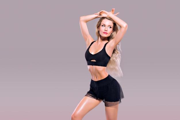 Charmantes sportliches mädchen, das in sportkleidung posiert und ihren schicken körper zeigt. gemischte medien