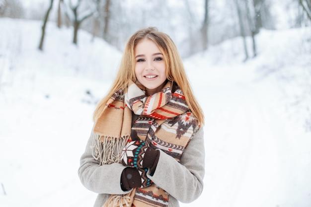 Charmantes süßes junges mädchen in einem winter stilvollen mantel in einem vintage wollschal in stilvollen warmen fäustlingen