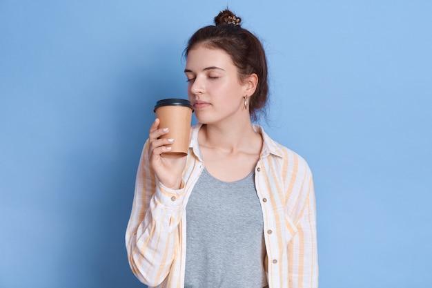 Charmantes süßes lässiges, dunkelhaariges, ziemlich faszinierendes mädchen, das ihren tee oder kaffee in pappbecher riecht und isolierte freizeithemden trägt.