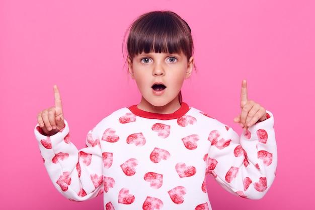 Charmantes überraschtes weibliches kind in lässigem pullover, der mit beiden zeigefingern nach oben zeigt, werbung für schockierende angebote, blick nach vorne mit erstauntem ausdruck, isoliert über rosa wand