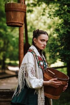 Charmantes ukrainisches mädchen in einem traditionellen kleid mit einem eimer in ihren armen