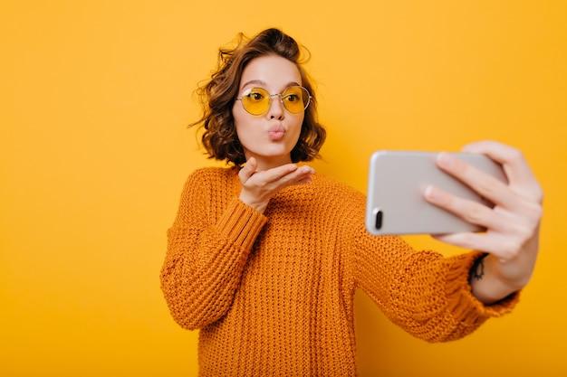 Charmantes weibliches modell, das luftkuss sendet, während selfie macht