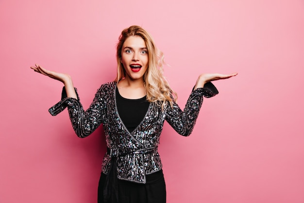 Charmantes weibliches modell in der glitzerkleidung, die auf rosa wand aufwirft. innenfoto des ekstatischen blonden mädchens stehend.