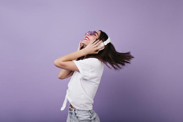 Charmantes weibliches modell in der sonnenbrille, die mit inspiriertem lächeln tanzt. innenfoto des raffinierten brünetten mädchens trägt große kopfhörer.