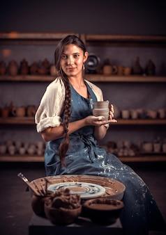 Charminghandicraftsman arbeitet mit ton auf einer töpferscheibe. handwerksproduktion.