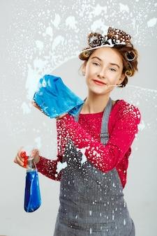 Charning junge frau wäscht fenster mit blauem handtuch