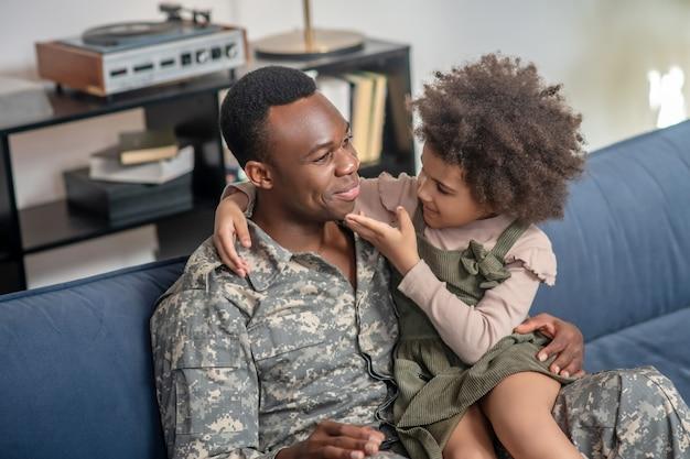 Chatten mit papa. kleines dunkelhäutiges, lockiges mädchen, das in den armen eines jungen erwachsenen glücklichen vaters in militäruniform auf dem sofa zu hause sitzt