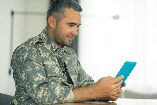Chatten sie mit der familie. servicemann, der ein tablet hält, während er mit der familie video-chat führt, während er sie vermisst