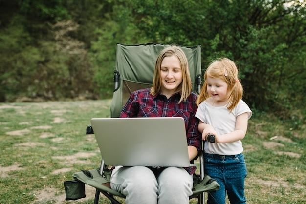 Chatten sie online mit ihrer familie auf einem laptop beim picknick in der natur. homeschooling, freiberuflicher job. mutter und kind. mutter arbeiten im internet mit kind im freien.