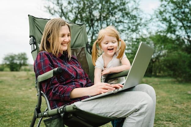 Chatten sie online mit ihrer familie auf einem laptop beim picknick in der natur