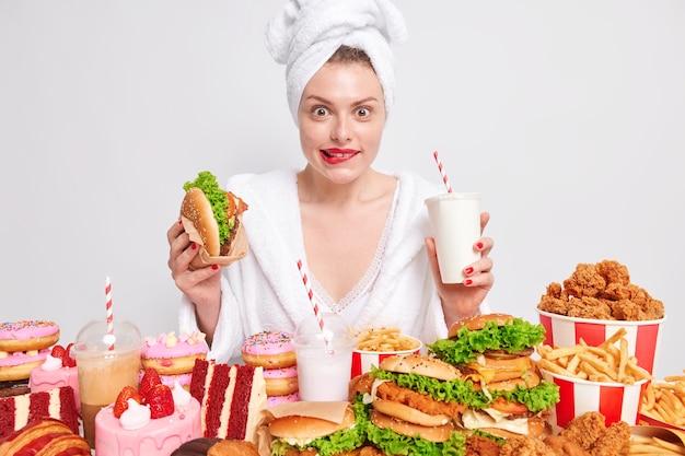 Cheat-mahlzeit ungesundes ernährungskonzept. erfreute dame beißt sich auf die lippen, als sie sich einen appetitlichen snack ansieht
