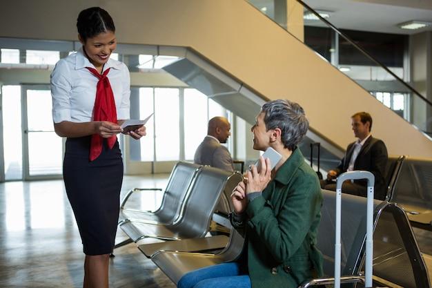 Check-in-mitarbeiter der fluggesellschaft, der den pass im wartebereich des check-in überprüft