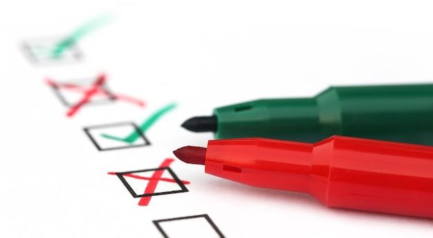 Checkliste mit grünem und rotem stift über weißem papier