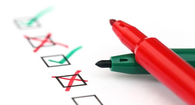 Checkliste mit zwei stiften auf weißem papier