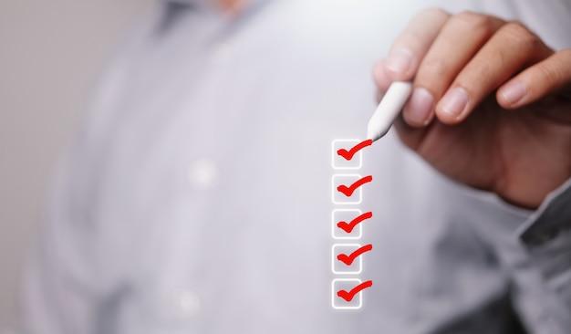 Checklistenkonzept, geschäftsmann häkchen auf den kontrollkästchen mit marker rot