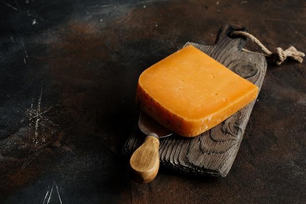 Cheddar-käse auf einem holzbrett auf einem dunklen hintergrund.