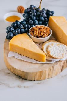 Cheddar-käse, trauben, nüsse, honig und cracker in holzbrett auf marmor