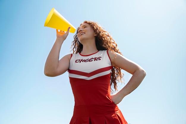 Cheerleader mit mittlerem schuss, niedriger winkel